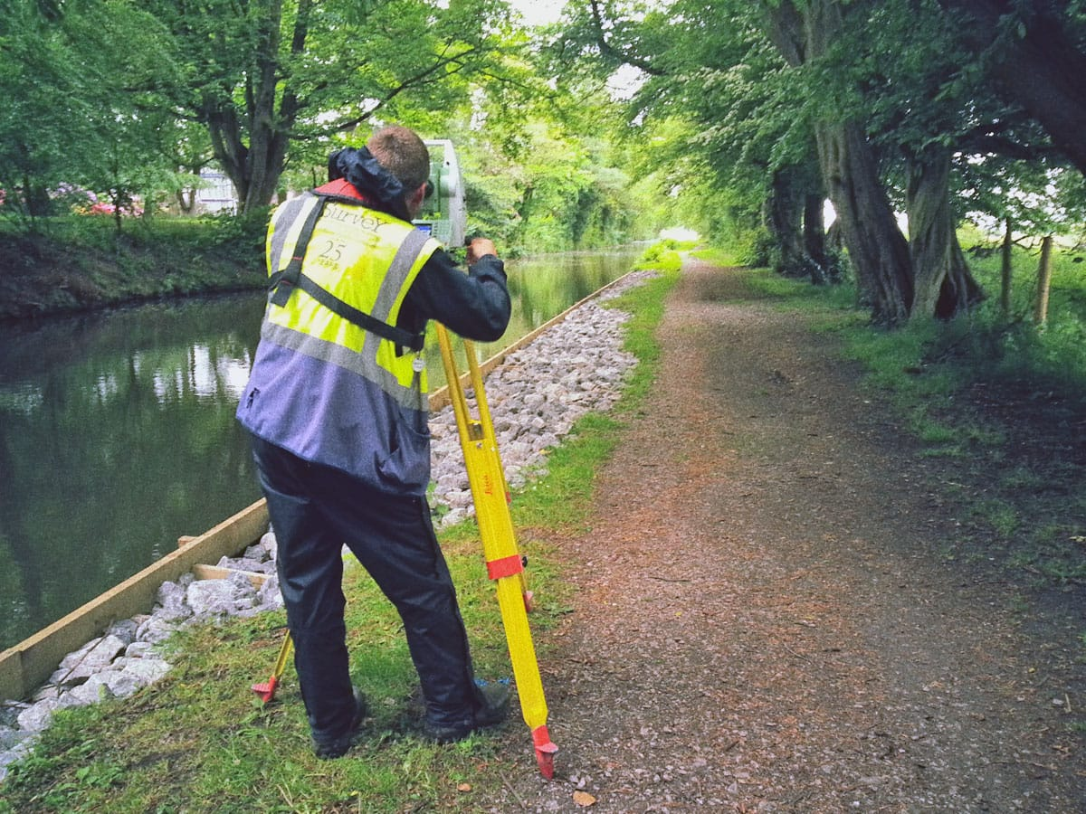Survey operations surveying near a canal.